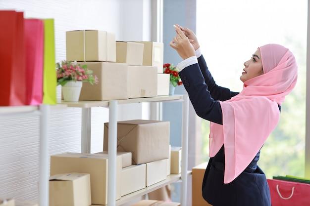 Bocznego widoku religijna azjatykcia muzułmańska kobieta w niebieskim kostiumu stoi i bierze obrazek pakunku pudełko dostarcza od telefonu komórkowego. początkowa mała firma mśp freelance kobieta pracuje w domu ze szczęśliwą uśmiechniętą twarzą