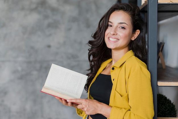 Bocznego widoku smiley dziewczyna z książką