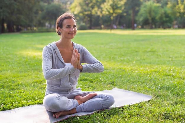 Bocznego widoku smiley kobieta medytuje pozę
