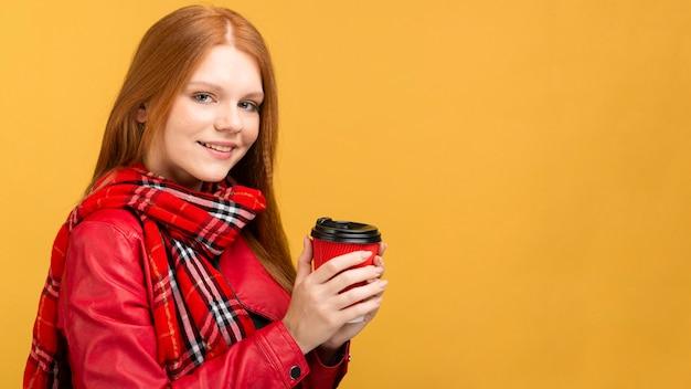 Bocznego widoku smiley kobieta trzyma filiżankę