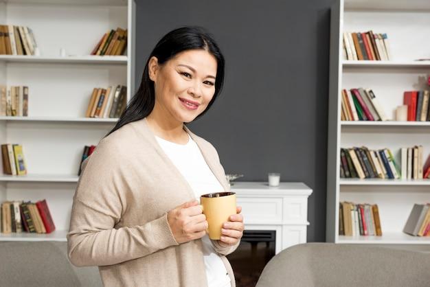 Bocznego widoku smiley kobieta z filiżanką kawy
