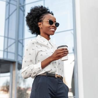 Bocznego widoku smiley kobieta z kawowy plenerowym