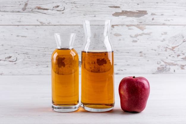 Bocznego widoku sok jabłkowy na białym drewnianym stole