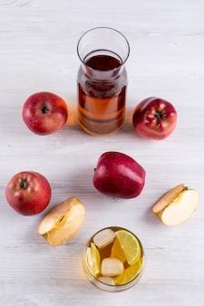 Bocznego widoku sok jabłkowy z czerwonymi jabłkami na białym drewnianym stole