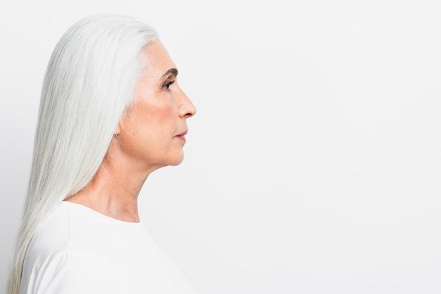 Bocznego widoku starsza kobieta patrzeje daleko od
