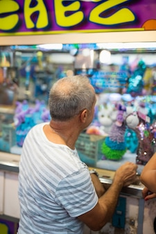 Bocznego widoku stary człowiek przy zabawka stojakiem
