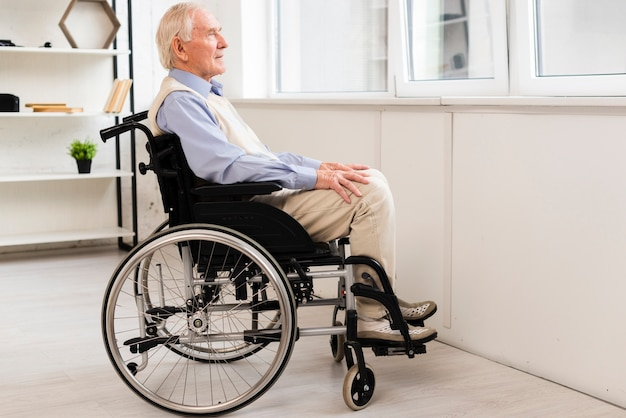 Bocznego widoku stary człowiek siedzi na wózku inwalidzkim