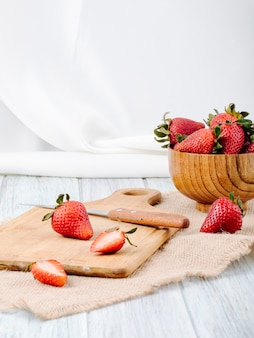Bocznego widoku świeża truskawka w pucharu nożu i deska na białym tle