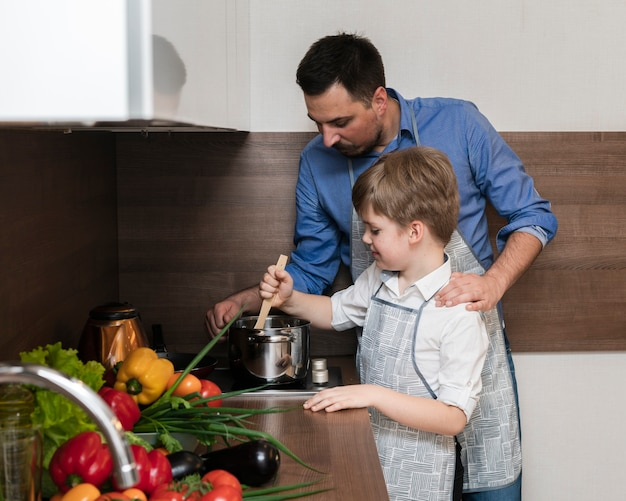 Bocznego widoku syn i ojciec gotuje wpólnie