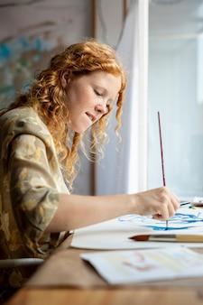 Bocznego widoku szczęśliwa kobieta maluje w domu