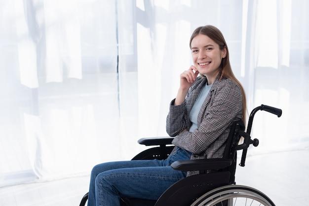 Bocznego widoku szczęśliwa kobieta na wózku inwalidzkim