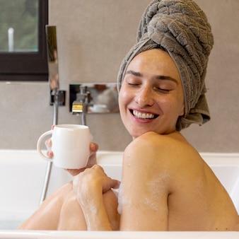 Bocznego widoku szczęśliwa kobieta z kubkiem w wannie