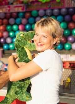 Bocznego widoku szczęśliwa kobieta z ślicznym dinosaurem