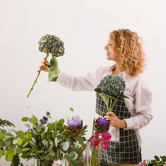 Bocznego widoku szczęśliwa kwiaciarnia trzyma up dwa bukieta