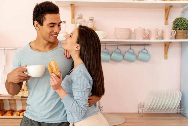 Bocznego widoku szczęśliwa para z pączkiem i filiżanką