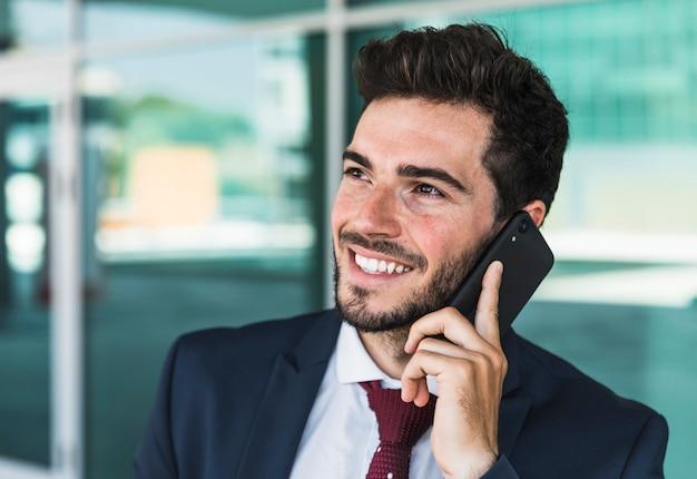 Bocznego widoku szczęśliwy mężczyzna z jego smartphone
