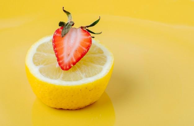 Bocznego widoku truskawka z plasterkiem cytryna na żółtym tle