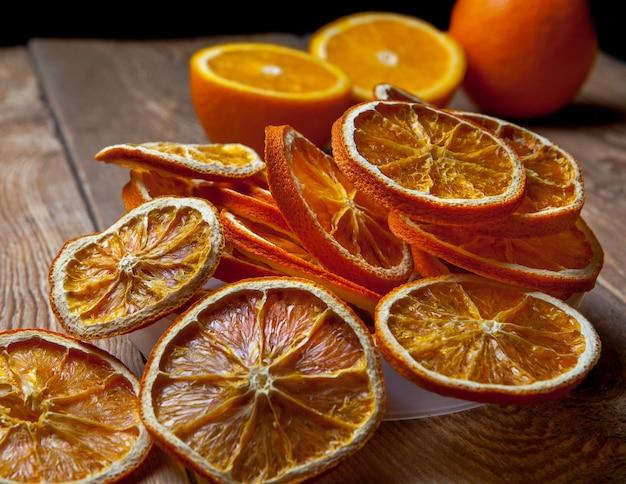 Bocznego widoku zakończenie suszył pomarańczowe i świeże pomarańcze na drewnianym stole