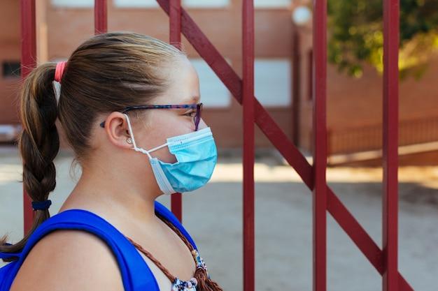 Boczny portret blondynki z niebieskim plecakiem i maską na twarz. powrót do szkoły.