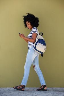Boczny portret młodej kobiety odprowadzenie z torbą i mądrze telefonem