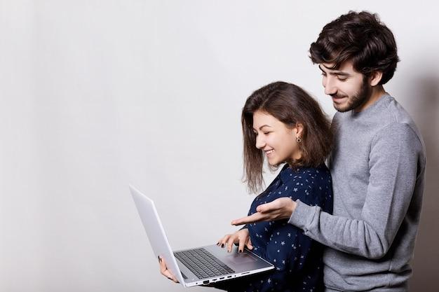 Boczny portret pięknej pary oglądającej filmy online, stojącej blisko siebie, trzymającej laptopa