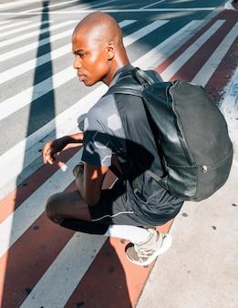 Boczny widok afrykański młody zdrowy mężczyzna z jego plecakiem kuca na drodze w mieście