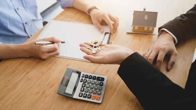 Boczny widok agenta nieruchomości mienia domu klucz jego klient
