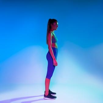 Boczny widok atlety pozycja z błękitnym blackground