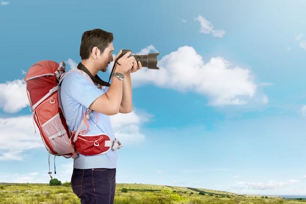 Boczny widok azjatykci fotografa mężczyzna z plecakiem