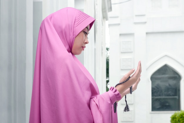 Boczny widok azjatykcia muzułmańska kobieta z modlitewnymi koralikami ono modli się