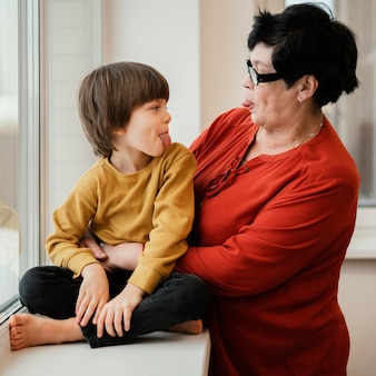 Boczny widok babci i wnuka grających i wystawiających swoje języki