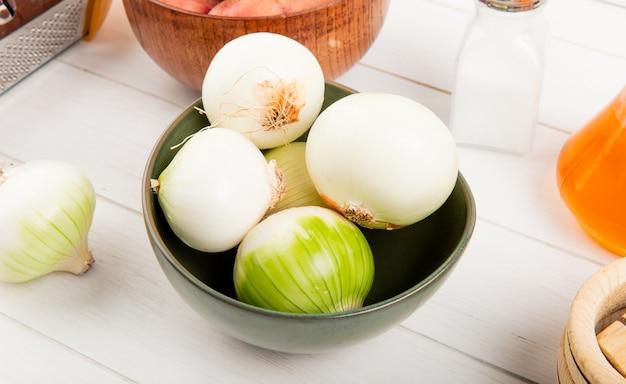 Boczny widok białe cebule w pucharze z grulami w pucharu soli masle wokoło na drewnianym tle