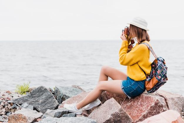 Boczny widok bierze fotografię podróżna kobieta