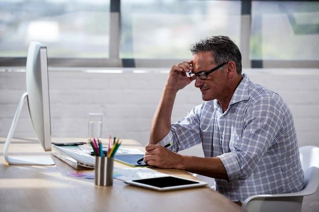Boczny widok biznesmen pracuje przy biurkiem