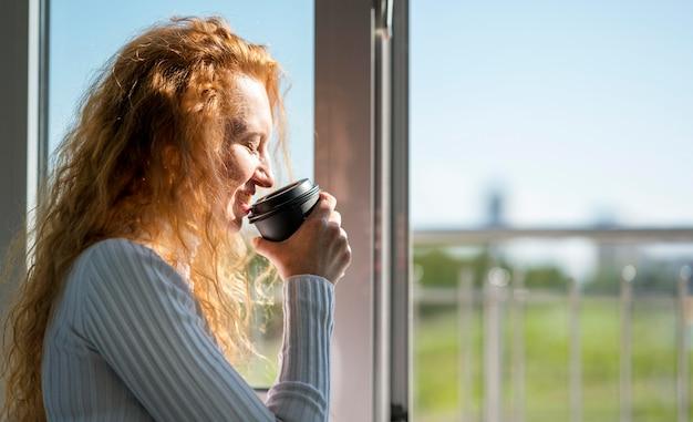 Boczny widok bizneswoman picia kawy