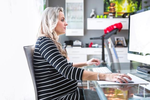 Boczny widok bizneswoman pracuje na komputerze