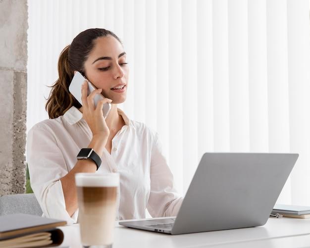 Boczny widok bizneswoman pracuje ze smartfonem i laptopem
