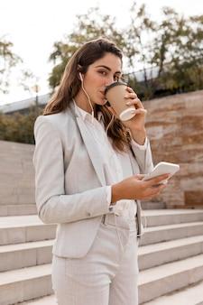 Boczny widok bizneswoman pracuje ze smartfonem i pije kawę