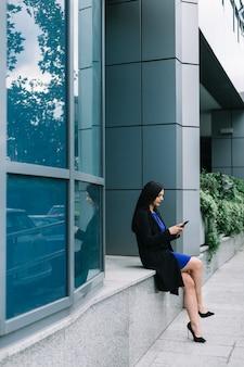 Boczny widok bizneswoman używa smartphone na zewnątrz budynku biurowego