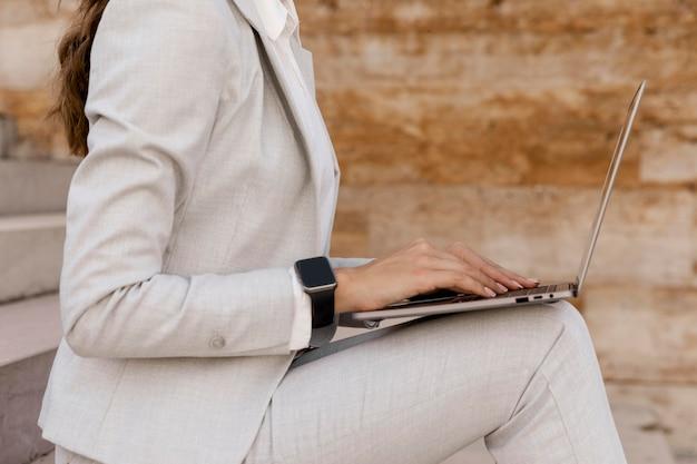 Boczny widok bizneswoman z smartwatch pracujący na laptopie na zewnątrz