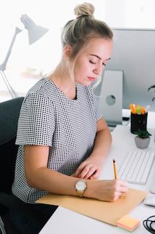 Boczny widok bizneswomanu writing na brown papierze nad białym biurkiem