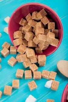 Boczny widok brown cukierek sześciany rozpraszający od menchii rzuca kulą na błękitnym drewnianym tle