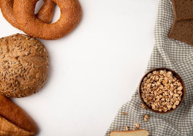 Boczny widok chleby jako cob bagel baguette żyto z pucharem pełno kukurudze na płótnie na białym tle z kopii przestrzenią