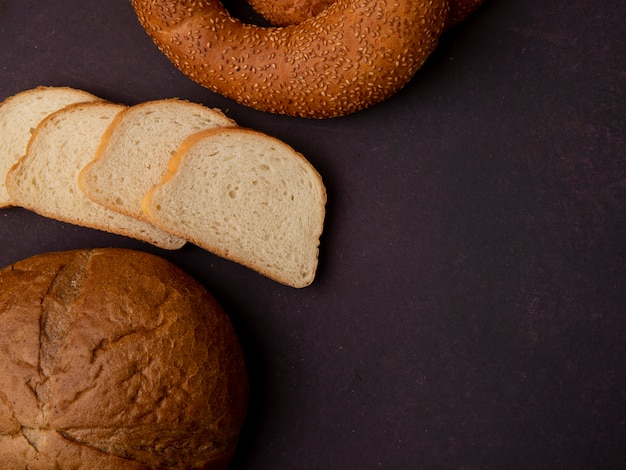 Boczny widok chleby jako klasyczni cob białego chleba plasterki i bagel na kasztanowym tle z kopii przestrzenią