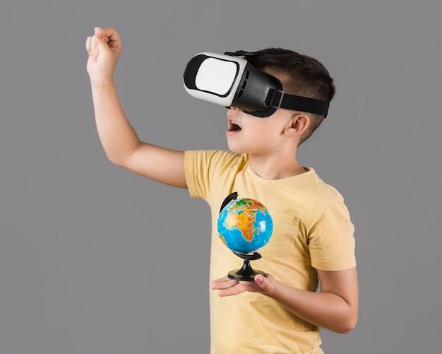 Boczny widok chłopiec z rzeczywistości wirtualnej słuchawki mienia kulą ziemską