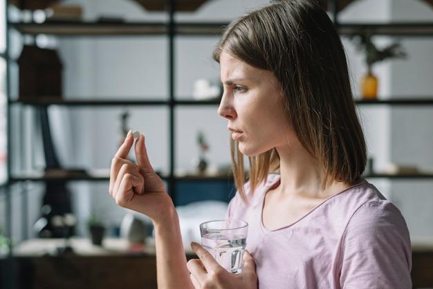 Boczny widok chora młoda kobieta patrzeje pigułkę
