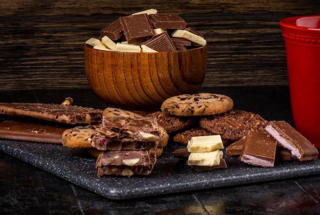 Boczny widok ciemna i biała czekolada w drewnianym pucharze i owsianych ciastkach rozpraszających na ciemnym tle