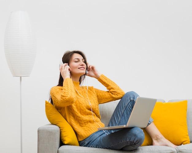 Boczny widok cieszy się jej muzykę na hełmofonach kobieta podczas gdy siedzący na kanapie