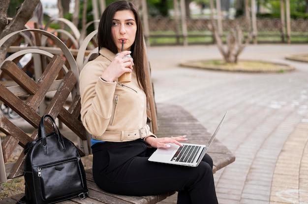 Boczny widok cieszy się napój kobieta outdoors podczas gdy pracujący na laptopie