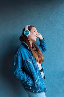 Boczny widok cieszy się słuchającą muzykę na hełmofonach kobieta